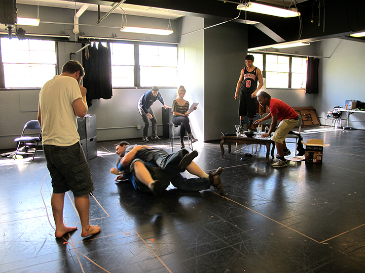 Tom Dewey works with the cast of The Financial Lives of the Poets on a fight scene, which devolves into wrestling.